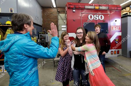 Stock Image of Sally Jewell Seventh grader Amanda Brown is surrounded by classmates congratulating her after finishing a rap song about what to do in an earthquake as Secretary of the Interior Sally Jewell, left, comes forward to high-five her following an earthquake drill as part of a statewide Great Shakeout drill at the Oso firehouse, in Oso, Wash. Jewell was in the area to view for the first time the devastation caused by last year's landslide off Highway 530 and to participate in the drill with school children from nearby Darrington, Wash