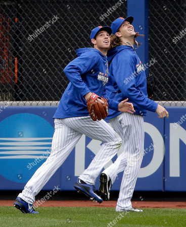 New York Mets pitchers Steven Matz, left, and Jacob deGrom chase after fly balls during batting practice, in New York. The Mets will face the Kansas City Royals in Game 1 of the World Series on Tuesday