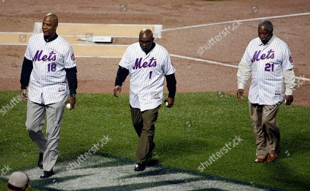 Cleon Jones, right to left, Mookie Wilson and Darryl Strawberry walk off the field after throwing the ceremonial first pitch before Game 5 of the Major League Baseball World Series between the New York Mets and the Kansas City Royals, in New York