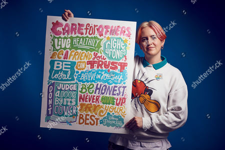 Kate Moross holding the Princess Principles poster she designed
