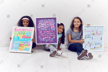 L to R: Samaria Gabbidon-Woolcock, Age 7,  Gracie Swan, Age 10, and Su Bogazkaya, Age 5 (all from London) holding Princess Principles posters by Kate Moross, Kate Forrester and Rose Blake respectively