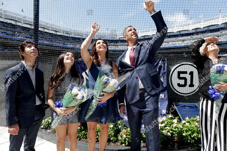 ADDS NAME OF MOTHER - Former New York Yankees catcher Jorge Posada, second from right, and his wife Laura Posada, third from left, wave to fans while standing inside Monument Park with his son, Jorge Posada Jr. and daughter Paulina Posada and mother Tamara de Posada before a baseball game against the Cleveland Indians, in New York. Posada's jersey number 20 was retired before the game