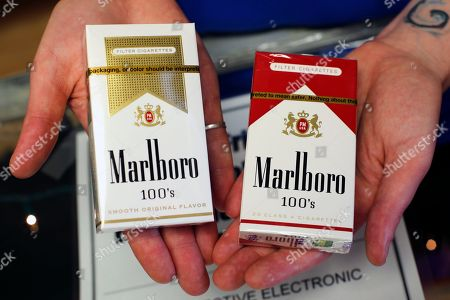 Altria; Marlboro; cigarettes Store manager Stephanie Hunt poses for photos with packs of Marlboro cigarettes, an Altria brand, at a Smoker Friendly shop in Pittsburgh
