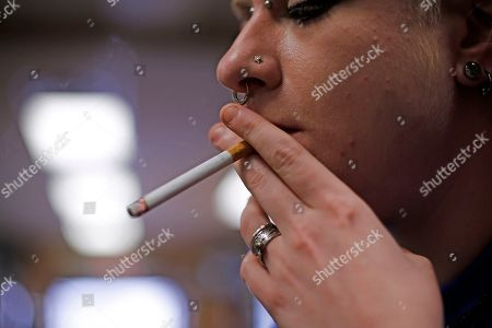 Altria; Marlboro; smoking; cigarettes Store manager Stephanie Hunt smokes a Marlboro cigarette while posing for photos at a Smoker Friendly shop in Pittsburgh