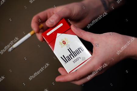 Stock Picture of Altria; Marlboro; cigarettes Store manager Stephanie Hunt poses for photos with a pack of Marlboro cigarettes at a Smoker Friendly shop in Pittsburgh