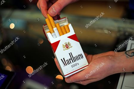 Altria; Marlboro; cigarettes Store manager Stephanie Hunt poses for photos with a pack of Marlboro cigarettes at a Smoker Friendly shop in Pittsburgh