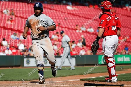 Jason Rogers, Tucker Barnhart Milwaukee Brewers' Jason Rogers, left, scores on a sacrifice fly by Domingo Santana as Cincinnati Reds catcher Tucker Barnhart, right, looks on in the ninth inning in the first game of a baseball doubleheader, in Cincinnati. The Brewers won 8-6