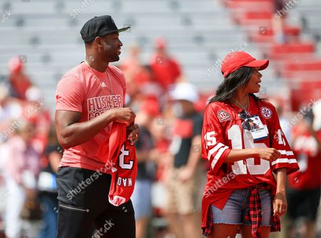 Gabrielle Union, Dwayne Wade Actress Gabrielle Union wears a Nebraska jersey as she poses for a photo with her husband Miami Heat's Dwayne Wade at Memorial Stadium before an NCAA college football game between Nebraska and Brigham Young in Lincoln, Neb