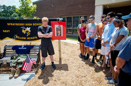 Jonathan Kent Student Jonathan Kent, 17, left, leads a moment of prayer with former and current classmates at a memorial outside the JROTC office at Sprayberry High School where Skip Wells attended, in Marietta, Ga. Wells was one of four Marines killed in Thursday's shooting in Chattanooga