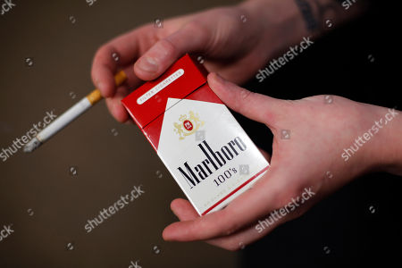 Store manager Stephanie Hunt poses for photos with a pack of Marlboro cigarettes, an Altria brand, at a Smoker Friendly shop in Pittsburgh. Altria reports quarterly financial results on