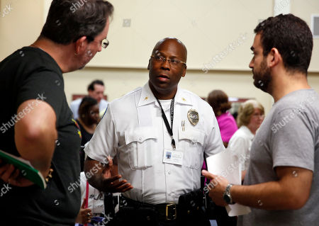 Andre Anderson, Marc DeSantis, John Powell Interim police chief Andre Anderson, center, talks with activists John Powell, left, and Marc DeSantis at the end of a city council meeting in Ferguson, Mo. Anderson says he wants his officers engaging with the community, getting out of their cars and mingling with people in an effort to build better relations