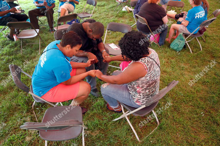 """Clockwise from bottom left, Kenyatta Smith, Andre Ford and Latoya Jackson pray during a gathering of various church groups dubbed """"A Day of Hope"""", Ferguson, Mo. More than 40 area churches along with help from Convoy of Hope organized the event to bring people together and offer everything from health screenings to job counseling to free groceries and more"""