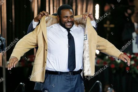 Stock Photo of Jerome Bettis, John Bettis III Pro Football Hall of Fame inductee Jerome Bettis slips into his gold jacket with help from his presenter and brother, John Bettis III, rear, during the gold jacket ceremony in Canton, Ohio