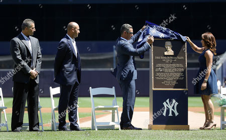 Former New York Yankees catcher Jorge Posada, third from left, and his wife Laura Posada, unveil Posada's plaque that will hang at Monument Park as former teammates Andy Pettitte, far left, and Derek Jeter look on before a baseball game against the Cleveland Indians, in New York