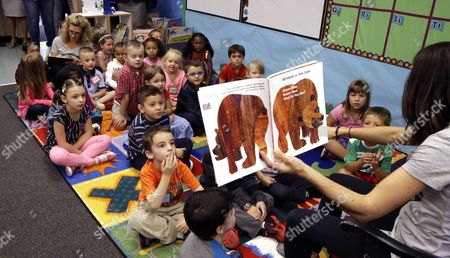 Stock Image of Kindergarten students listen to teacher Amy Holland reads on the first day of school at Nancy Ryles Elementary School in Beaverton, Ore., . Oregon Gov. Kate Brown visited the school kicking off the first school year with full-day kindergarten statewide