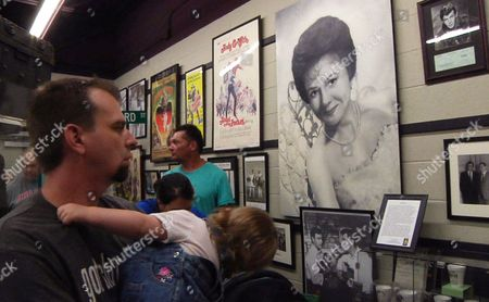 Stock Picture of A fan looks at a young glamour shot of actress Betty Lynn at the Andy Griffith Museum in Mount Airy, N.C, on . Every third Friday of the month, the 88-year-old star, who played Thelma Lou on Griffith's iconic television show, greets visitors to the museum by signing autographs, taking photos and blowing kisses