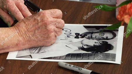 """Actress Betty Lynn signs a photo of her character, Thelma Lou, kissing """"Deputy Barney Fife"""" played by actor Don Knotts, during her autograph event at the Andy Griffith Museum in Mount Airy, N.C., on . Every third Friday of the month, the 88-year-old star greets visitors to the museum by signing autographs, taking photos and blowing kisses"""