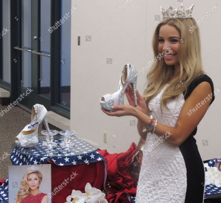 "Miss America Kira Kazantsev holds the shoes she will wear in this week's ""Show Us Your Shoes"" parade on the Atlantic City, N.J. Boardwalk during a news conference in Atlantic City, several hours before the first night of preliminary competition to choose her successor"