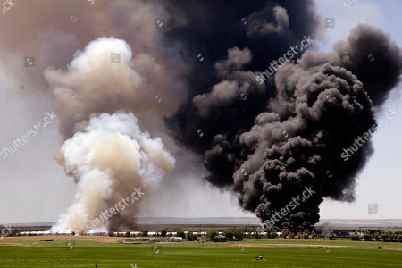 Stock Picture of Two giant columns of smoke rise above a fire burning several buildings at the Inland Trap & Liner company, in Moses Lake, Wash. Grant County Sheriff's spokesman Kyle Foreman said no one was injured, but the fire has caused one propane tank to explode, sending a mushroom cloud 1,000 feet into the air. Numerous haystacks also burned