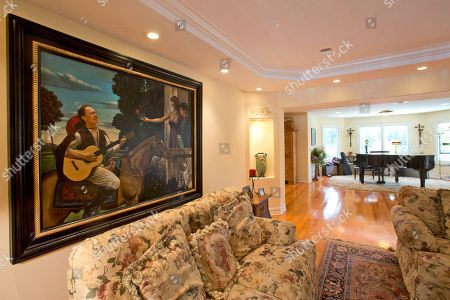 This photo shows a painting depicting 1970's heartthrob David Cassidy, left, his son, a parrot and soon-to-be ex-wife hangs in his five-bedroom Florida mansion in Fort Lauderdale, Fla. Cassidy, 65, is auctioning the waterfront home and all its furnishings Sept. 9 as part of bankruptcy and divorce proceedings