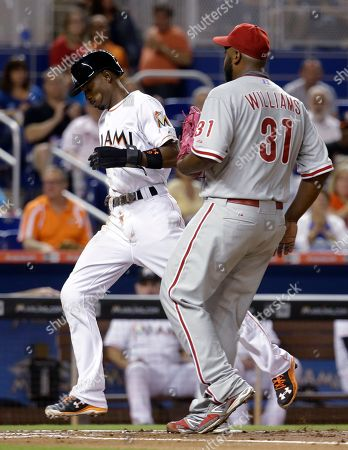 Dee Gordon, Jerome Williams Miami Marlins' Dee Gordon runs past Philadelphia Phillies starting pitcher Jerome Williams (31) to score on a wild pitch during the first inning of a baseball game, in Miami
