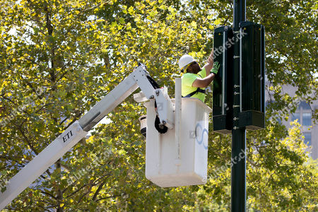 Technician Kevin Wallace with Crown Castle works on a mobile phone communication equipment, along the Benjamin Franklin Parkway in Philadelphia. On the parkway Pope Francis is scheduled to visit The World Meeting of Families' festival and celebrate a Mass during his visit to the United States