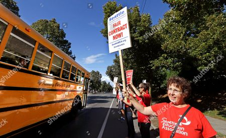 A private school bus passes as West Seattle High School teacher Jennifer Hall pickets with about 50 colleagues outside the school, in Seattle. As the Pasco teachers strike enters its second day, teachers, parents and school officials in Seattle and Spokane prepare for possible strikes in the state's two largest school districts