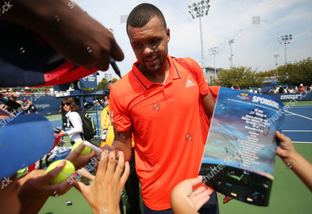 Jo-Wilifried Tsonga, of France, signs autographs for fans after beating Jarkko Nieminen, of Finland, during the first round of the U.S. Open tennis tournament, in New York