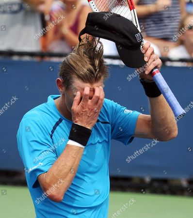 Jarkko Nieminen, of Finland, wipes sweat from his forehead between points during the first round of the U.S. Open tennis tournament against Jo-Wilifried Tsonga, of France, in New York