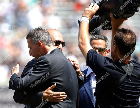 Derek Jeter, Andy Pettitte Retired New York Yankees players greet former Yankees pitcher Andy Pettitte, front left, who embraces Derek Jeter as Pettitte's number was retired before the Yankees' baseball game against the Cleveland Indians in New York