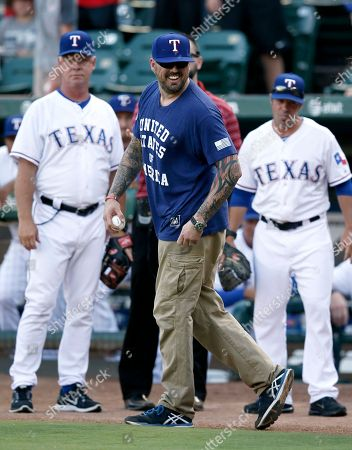 Marucs Luttrell Former Navy Seal Marcus Luttrell, in blue, walks out to throw out the ceremonial first pitch before a baseball game between the New York Yankees and Texas Rangers, in Arlington, Texas