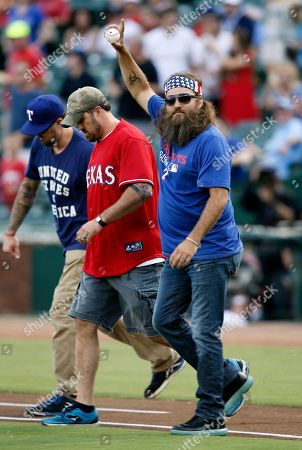 Willie Robertson, Morgan Luttrell, Marcus Luttrell Willie Robertson, CEO of Duck Commander acknowledges cheers from fans as he walks out to throw a ceremonial first pitch before a baseball game between the New York Yankees and Texas Rangers, in Arlington, Texas. Former Navy Seals Morgan Luttrell, center, and his twin brother Marcus joined Robertson during the pregame ceremony