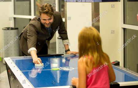 Recording artist Luke Wade play air hockey with a child at Children's Healthcare of Atlanta at Scottish Rite, in in Atlanta