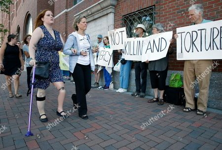 Boston Marathon bombing victim Erika Brannock, foreground left, and her mother Carol Downing, foreground right, walk past demonstrators outside federal court in Boston, . More than 20 victims of the Boston Marathon bombing and their family members are expected to address the court regarding the attack's impact on their lives before a judge formally sentences bomber Dzhokhar Tsarnaev to death