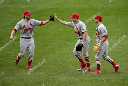 St. Louis Cardinals' Mark Reynolds (12), Peter Bourjos (8) and Randal Grichuk (15) celebrate after their baseball game against the Kansas City Royals, in Kansas City, Mo. The Cardinals won 6-1