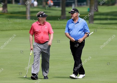 Michael Allen, left, talks with John Jacobs on the 18th fairway during the first round of the Encompass Championship golf tournament, in Glenview, Ill