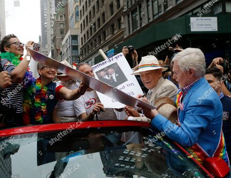 Ian McKellan, Derek Jacobi Actors Sir Ian McKellan, second from right, watches as Sir Derek Jacobi autographs a poster for two legally married women, left, before the start of the Heritage Pride March in New York, . The two actors were grand marshals for New York's gay pride march and parade. A large turnout was expected for gay pride parades across the U.S. following the landmark Supreme Court ruling that said gay couples can marry anywhere in the country