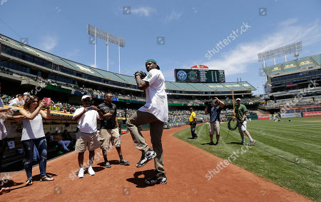 Festus Ezeli Golden State Warriors center Festus Ezeli practices for throwing out the ceremonial first pitch before a baseball game between the Oakland Athletics and the Seattle Mariners in Oakland, Calif