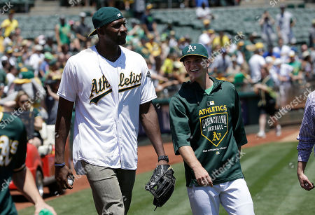 Festus Ezeli, Sonny Gray Golden State Warriors center Festus Ezeli, left, prepares to throw out the ceremonial first pitch with Oakland Athletics pitcher Sonny Gray before a baseball game between the Athletics and the Seattle Mariners in Oakland, Calif