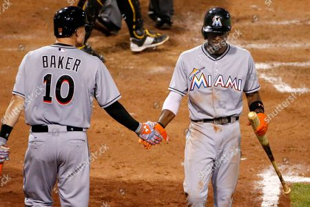 Stock Photo of Dee Gordon, Jeff Baker Miami Marlins' Dee Gordon, right, is greeted by teammate Jeff Baker (10) after scoring on a double by Martin Prado in the seventh inning of a baseball game against the Pittsburgh Pirates in Pittsburgh