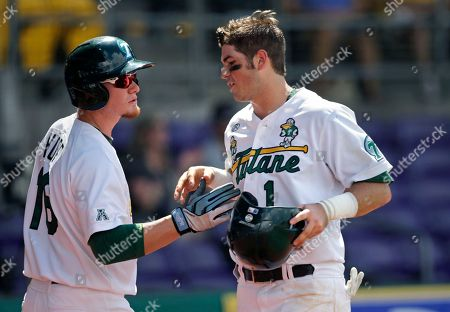 Tulane's Garrett Deschamp (1) is greeted at the dugout by Hunter Hope (16) after scoring on an RBI double against Lehigh at the Baton Rouge Regional of the NCAA college baseball tournament in Baton Rouge, La