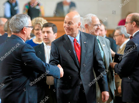 Pete Ricketts, Dan Hughes Nebraska Gov. Pete Ricketts, center, shakes the hand of Sen. Dan Hughes of Venango, after addressing the Legislature in Lincoln, Neb., on the last day of a legislative session that included a gas tax increase, the repeal of a ban on driver's licenses for young immigrants and the abolition of the death penalty