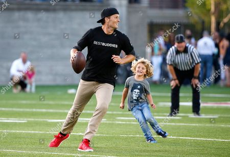 Tom Brady New England Patriots' Tom Brady runs from Joseph Shriver, son of Anthony Kennedy Shriver, during a Best Buddies Challenge charity football game in Boston