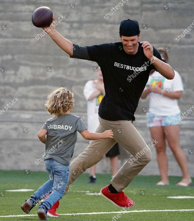 Tom Brady, Josehp Shriver New England Patriots' Tom Brady, right, runs from Joseph Shriver, son of Anthony Kennedy Shriver, during a Best Buddies Challenge charity football game in Boston