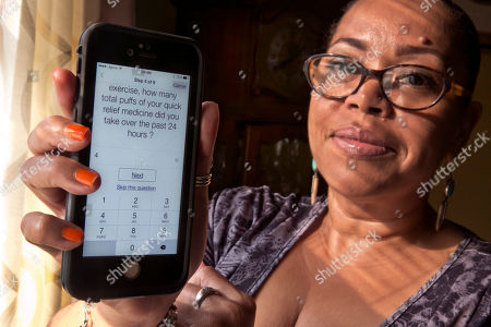 Stock Image of Elizabeth Ortiz Asthma sufferer Elizabeth Ortiz, who uses the Asthma Health smartphone app daily to track her condition, poses for photos at her apartment, on New York's Lower East Side. Ortiz measures her lung power each day by breathing into an inexpensive plastic device and then typing the results into the app, which also asks if she's had difficulty breathing or sleeping, or taken medication that day