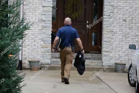 Federal authorities walk outside of the home of Subway restaurant spokesman Jared Fogle, in Zionsville, Ind. FBI agents and Indiana State Police have removed electronics from the property