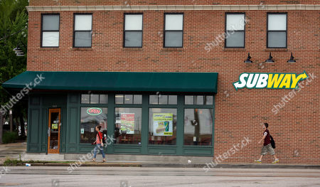 People walk past a Subway restaurant, in St. Louis. A raid at the home of Subway spokesman Jared Fogle is just the latest bad news to hit the sandwich chain. The company has been struggling with sales, its CEO is being treated for cancer and it's trying to convince customers about the quality and value of its food