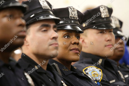Police officers who are members of the Summer All Out community policing program listen as New York City Police Commissioner William J. Bratton and Mayor Bill de Blasio speak to reporters during a news conference to discuss the program, in the Bronx borough of New York