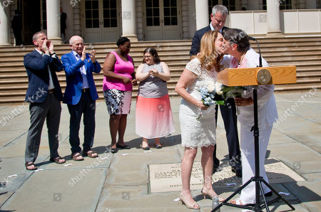 Gay Marriage Mayor Bill de Blasio stands behind Cindy Jackson, second from right, and her partner Denise Niewinski, far right, as they kiss after he married the couple at City Hall to celebrate the Supreme Court's ruling that now allows same-sex marriage in all 50 states, in New York. The mayor followed with a second wedding for Katrina Council, third from left, and her partner Sarah Jones, third from right, and a vow renewal for Thomas Kirdahy, far left, and his partner Terrence McNally, second from left