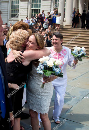 Stock Photo of Gay Marriage Cindy Jackson, center, is embraced after marrying her partner Denise Niewinski, right, at City Hall to celebrate the Supreme Court's ruling that now allows same-sex marriage in all 50 states, in New York